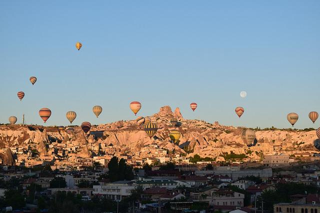朝日に照らされる気球とウチヒサル城と月