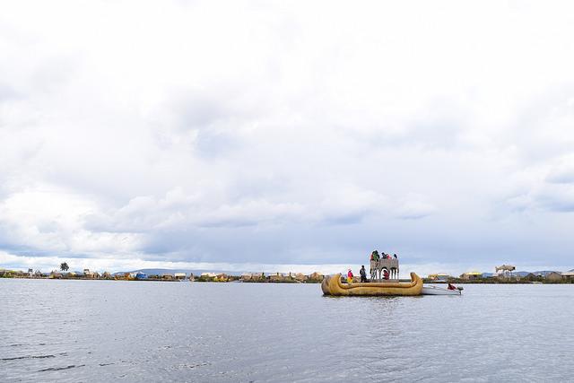 伝統的なボートを近代的なボートで押す光景